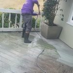 Hard day at work cleaning a deck off with pressure washing