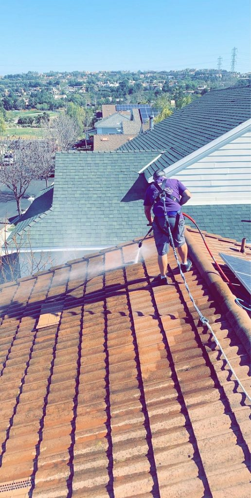 On top of a roof in the OC, cleaning the roof with our pressure washing machine